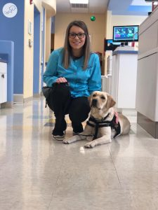 facility dog and dental assistant in pediatric dental office.